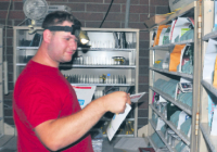 The power went out at the Ferndale Post Office on Monday, but employees still worked through the darkness using natural light and, in the darker parts of the building, headlamps. Ferndale rural carrier Konrad Riggan doesn't let the outage stop his work. (Brent Lindquist/Ferndale Record)