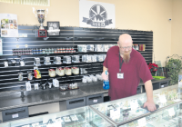 Buds SOS employee Chazz Komac tidies up the shop. Buds SOS is currently the only retail marijuana store in Ferndale, but applications are now being accepted for a second store. (Brent Lindquist/Ferndale Record)